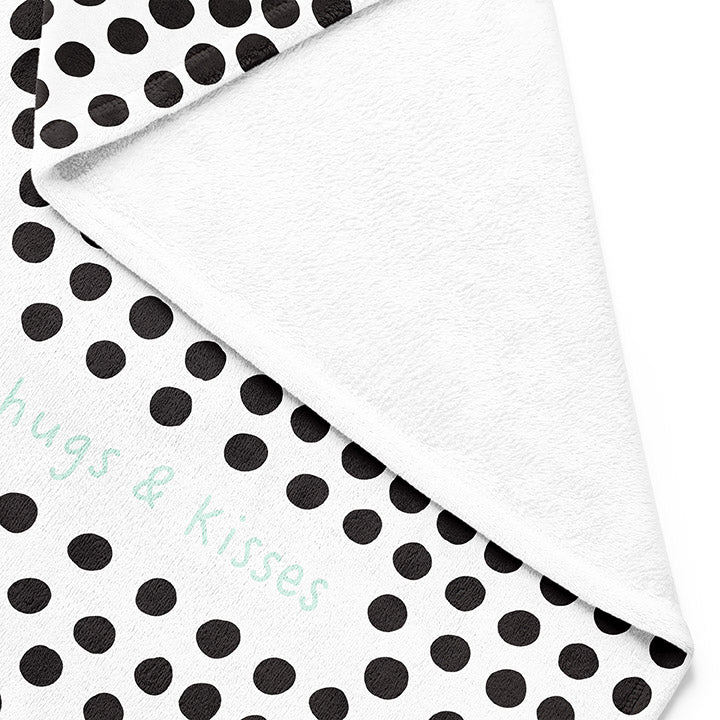 Backside of white 30 by 40 inch silky-soft fleece blanket that is hypoallergenic. Perfect size for a toddler or child. Bright white blanket printed on one side only. 3 inch hand drawn black dots scattered across blanket with the words hugs & kisses hand drawn in a mint green color. A small Adoptionly Yours heart logo by itself in mint green in lower left corner of blanket on front.