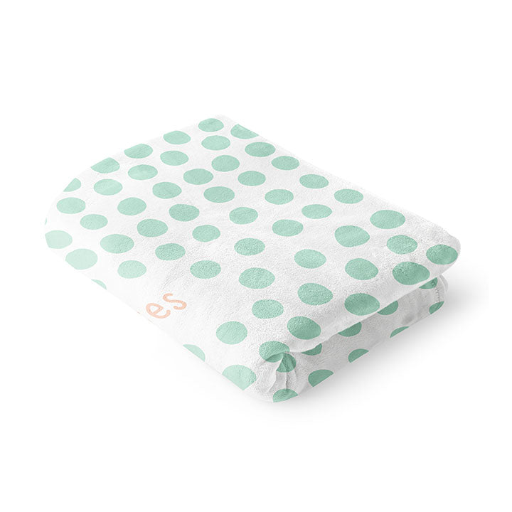 Folded 30 by 40 inch silky-soft fleece blanket that is hypoallergenic. Perfect size for a toddler or child. Bright white blanket printed on one side only. 3 inch hand drawn mint green dots scattered across blanket with the words hugs & kisses hand drawn in a peach color. A small Adoptionly Yours heart logo by itself in mint green in lower left corner of blanket on front.