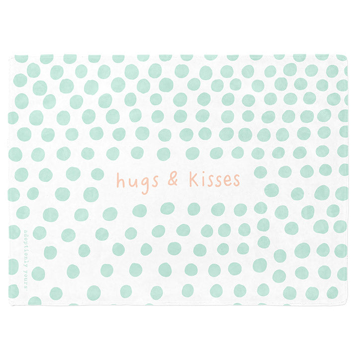 50 by 60 inch silky-soft fleece blanket that is hypoallergenic. Perfect size for a toddler or child. Bright white blanket printed on one side only. 4 inch hand drawn dots scattered across blanket in mint green with the words hugs & kisses hand drawn in a peach color. The words adoptionly yours in mint green typewriter font on lower left corner of blanket on front.