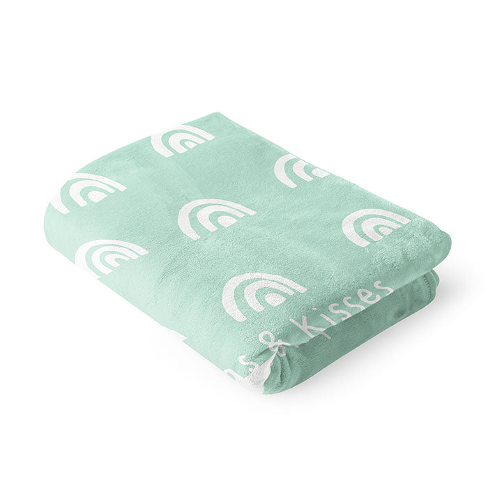 Folded 30 by 40 inch silky-soft fleece blanket that is hypoallergenic. Perfect size for a toddler or child. Bright white blanket printed on one side only. 4 rows of hand drawn rainbows in white with the words hugs & kisses hand drawn in white on a mint green background color. A small Adoptionly Yours heart logo by itself in white in lower left corner of blanket on front.