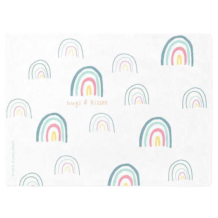 30 by 40 inch silky-soft fleece blanket that is hypoallergenic. Perfect size for a toddler or child. Bright white blanket printed on one side only. 15 large and small hand drawn rainbows scattered across blanket in magenta, light teal, bright yellow and green with the words hugs & kisses hand drawn in peach color. The words adoptionly yours in light teal typewriter font on lower left corner of blanket on front.