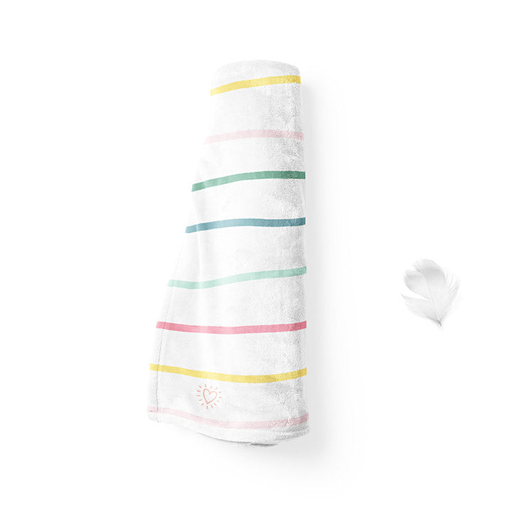 Rolled up 50 by 60 inch silky-soft fleece blanket that is hypoallergenic. Perfect size for an adult. Bright white blanket printed on one side only. 13 colorful hand drawn stripes of pink, green, blue, light teal, magenta and bright yellow run horizontally with the words xoxo, always in typewriter font. Adoptionly Yours heart logo by itself in pink in lower left corner of blanket on front.