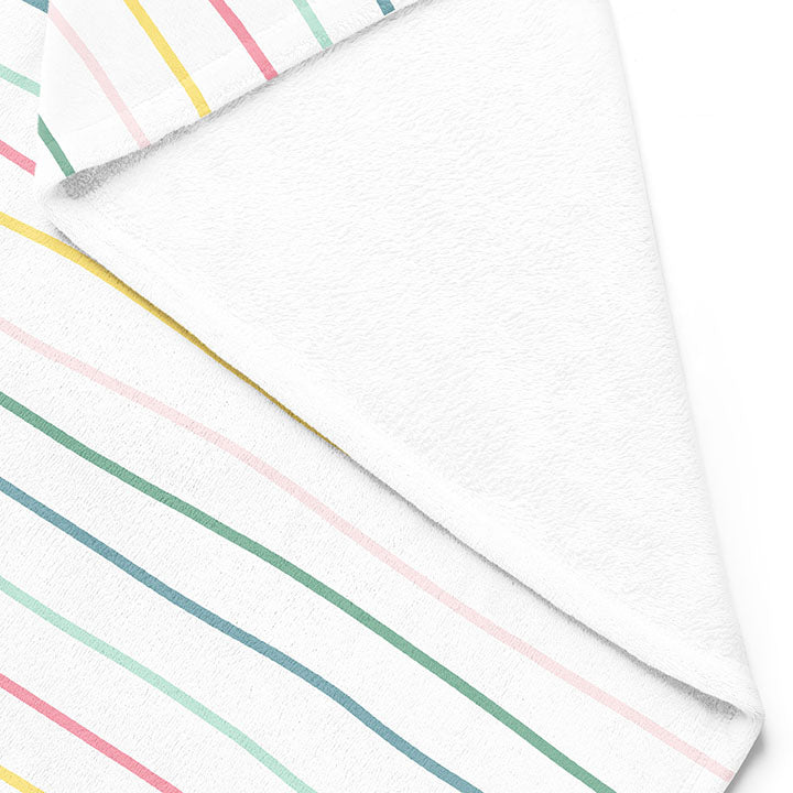 Backside of white 50 by 60 inch silky-soft fleece blanket that is hypoallergenic. Perfect size for an adult. Bright white blanket printed on one side only. 13 colorful hand drawn stripes of pink, green, blue, light teal, magenta and bright yellow run horizontally with the words xoxo, always in typewriter font. Adoptionly Yours heart logo by itself in pink in lower left corner of blanket on front.