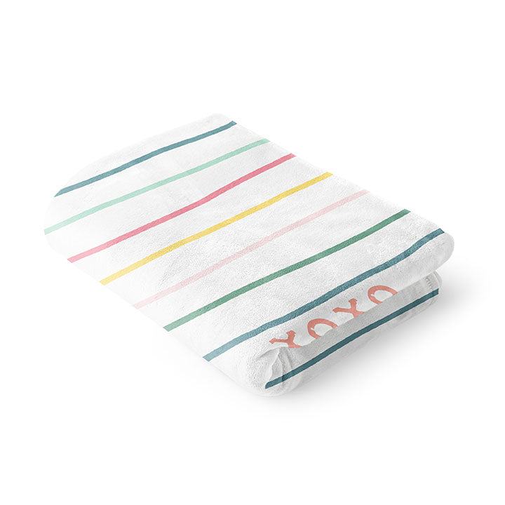 Folded 50 by 60 inch silky-soft fleece blanket that is hypoallergenic. Perfect size for an adult. Bright white blanket printed on one side only. 13 colorful hand drawn stripes of pink, green, blue, light teal, magenta and bright yellow run horizontally with the words xoxo, always in typewriter font. Adoptionly Yours heart logo by itself in pink in lower left corner of blanket on front.