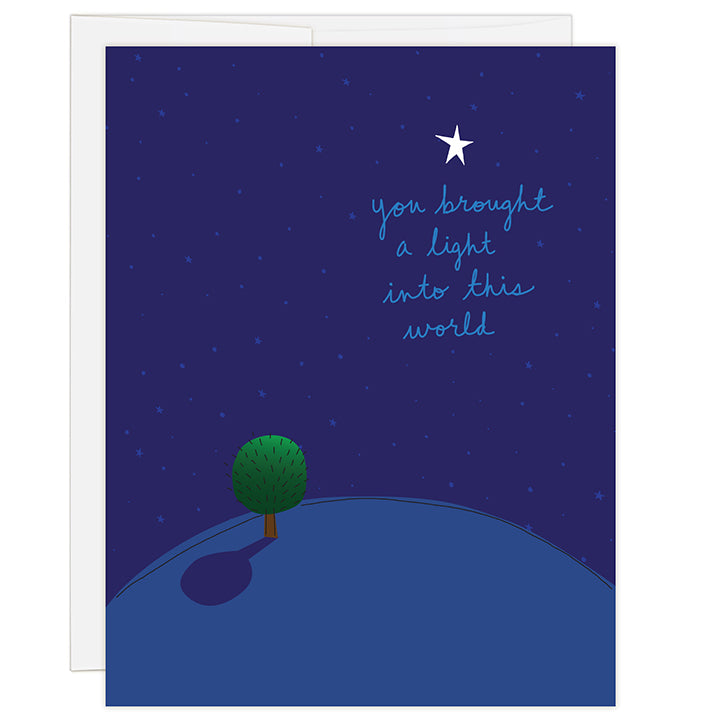 4.25 x 5.5 inch greeting card. Blank inside. Simple illustration style. Title You Brought A Light Into This World. Main image of dark blue background with an illustration of a small green tree on a small earth with one bright white star above title.