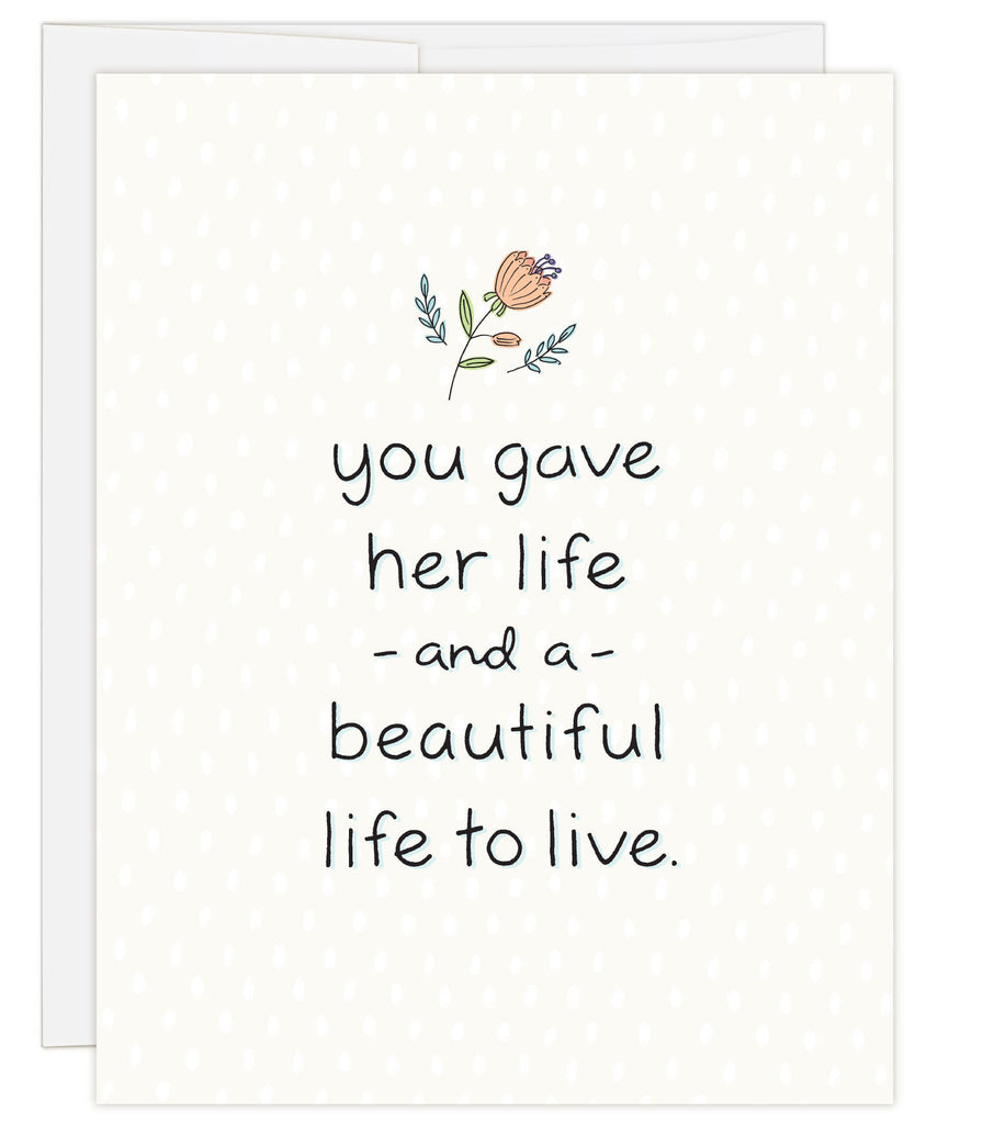 4.25 x 5.5 inch greeting card. Blank inside. Simple illustration style. Cream background with small salmon colored flower above title. Title You Gave Her Life and a Beautiful Life to Live.