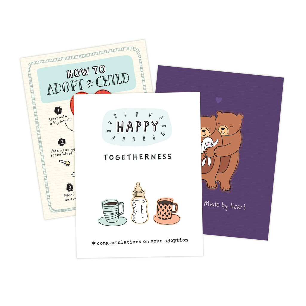 Three 4.25 x 5.5 inch greeting cards in a stack. Top card title reads Happy Togetherness. Congratulations on your adoption. Illustration of two coffee cups and one baby bottle with milk in the middle.