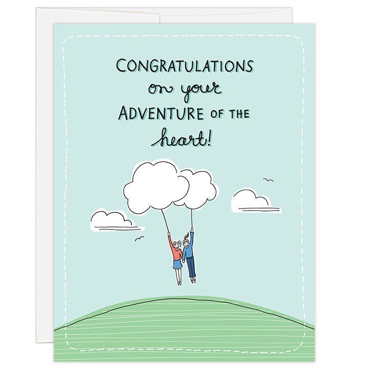 4.25 x 5.5 inch greeting card. Blank inside. Simple and charming illustration style. Title Congratulations on your adventure of the heart! Drawing of two women holding hands and each holding a string attached to a cloud that is floating above a green earth.