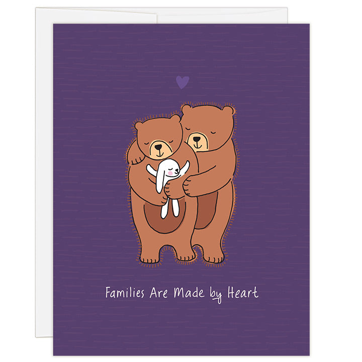 4.25 x 5.5 inch adoption greeting card. Blank inside. Simple and charming illustration style. Title Families Are Made by Heart. Main image is two brown bears with eyes closed and smiling while hugging a small white bunny rabbit with eyes closed and hugging bear back.
