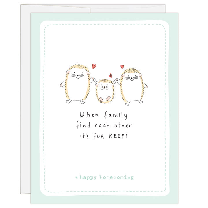4.25 x 5.5 inch greeting card. Blank inside. Simple and charming illustration style. Title When family find each other it's FOR KEEPS. Sub title *happy homecoming. Main image is two adult hedgehogs and one child hedgehog in center. They are holding hands and small red hearts above hedgehogs.
