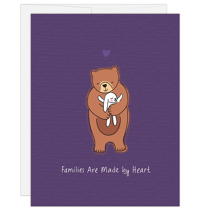 4.25 x 5.5 inch greeting card. Blank inside. Simple and charming illustration style. Title Families Are Made by Heart. Main image is one brown bear with eyes closed and smiling while hugging a small white bunny rabbit with smile and eyes closed hugging bear back.