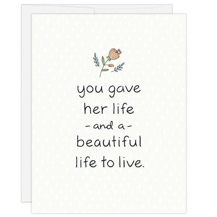 4.25 x 5.5 inch greeting card. Blank inside. Simple and charming illustration style. Cream background with small salmon colored flower above title. Title You Gave Her Life and a Beautiful Life to Live.