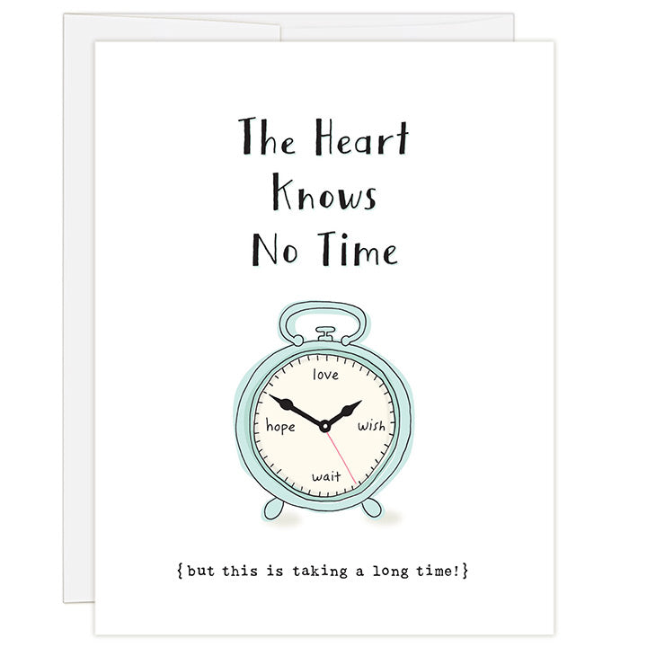 4.25 x 5.5 inch greeting card. Blank inside. Simple and charming illustration style. Title The Heart Knows No Time. Sub title {but this is taking a long time!} Main image is a clock with the words love, wish, wait, hope instead of numbers.
