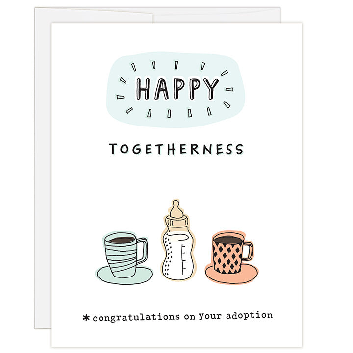 4.25 x 5.5 inch adoption congratulations greeting card. Blank inside. Simple illustration style. Title Happy Togetherness. Sub title *congratulations on your adoption. Illustration of two coffee cups and one baby bottle with milk in the middle.