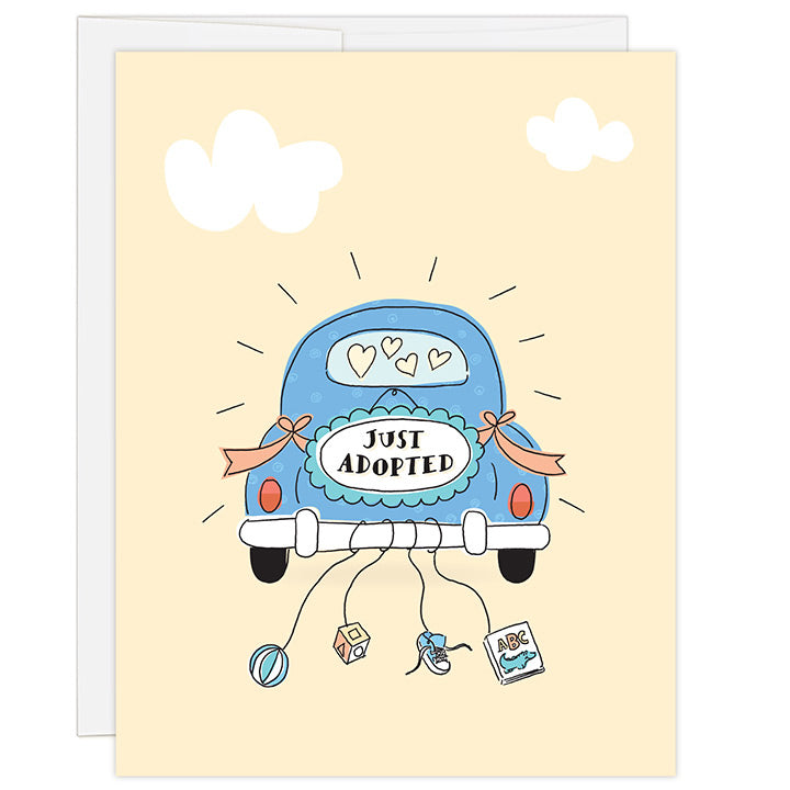 4.25 x 5.5 inch greeting card. Blank inside. Simple and charming illustration style. Sign on back of a dark blue antique car that reads JUST ADOPTED. Strings hang from the back bumper of the car with a ball, wooden block, toddler tennis show and abc's baby book.