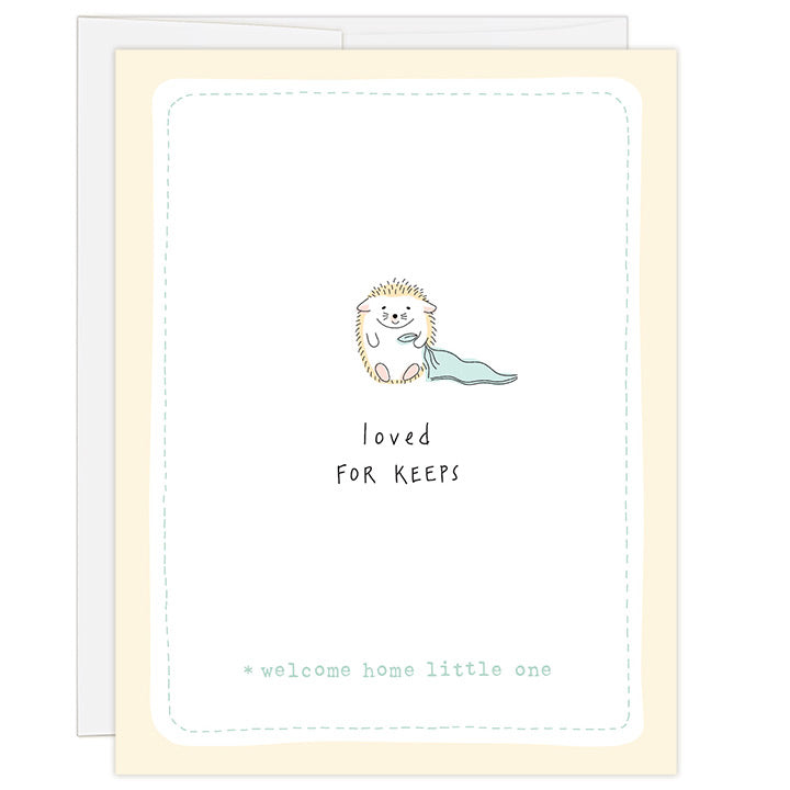 4.25 x 5.5 inch greeting card. Blank inside. Simple and charming illustration style. Title Loved FOR KEEPS. Sub title *welcome home little one. Main image is one baby hedgehog holding the corner of a small green blanket.