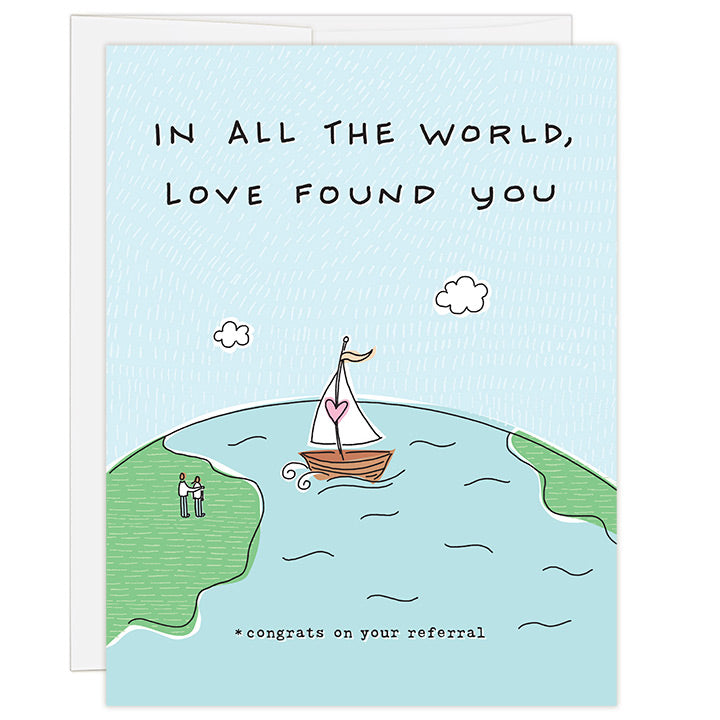 4.25 x 5.5 inch greeting card. Blank inside. Simple and charming illustration style. Title In All The World, Love Found You. Subtitle *congrats on your referral. Drawing of the earth with a sailboat crossing the sea to a couple on land. Sailboat has a pink heart on the mast of the sailboat.