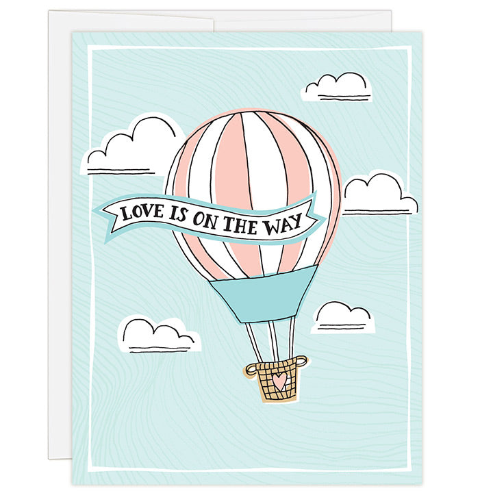 4.25 x 5.5 inch greeting card. Blank inside. Simple and charming illustration style. Title Love Is On The Way. Drawing of a pink stripped hot air balloon with a brown woven basket rising high up in the sky with white fluffy clouds. Title is in a ribbon draped across the hot air balloon.