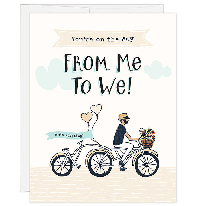 4.25 x 5.5 inch greeting card. Blank inside. Simple illustration style. Title You're on the Way From Me to We! Sub title *i'm adopting! Main image is man on tandem bicycle with flowers in basket and balloons on back. Back seat is empty.