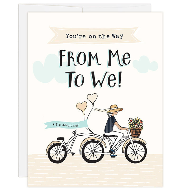 4.25 x 5.5 inch greeting card. Blank inside. Simple and charming illustration style. Title You're on the Way From Me to We! Sub title *i'm adopting! Main image is a woman on a tandem bicycle and back seat is empty. There are flowers in the basket and balloons on the back with the words i'm adopting! Adoption greeting card for supporting a single woman on the adoption journey.