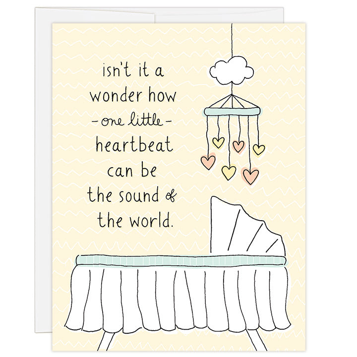 4.25 x 5.5 inch greeting card. Blank inside. Simple and charming illustration style. Title Isn't it a wonder how one little heartbeat can be the sound of the word. Drawing of a white basinet with a mobile hanging above with peach and yellow hearts.