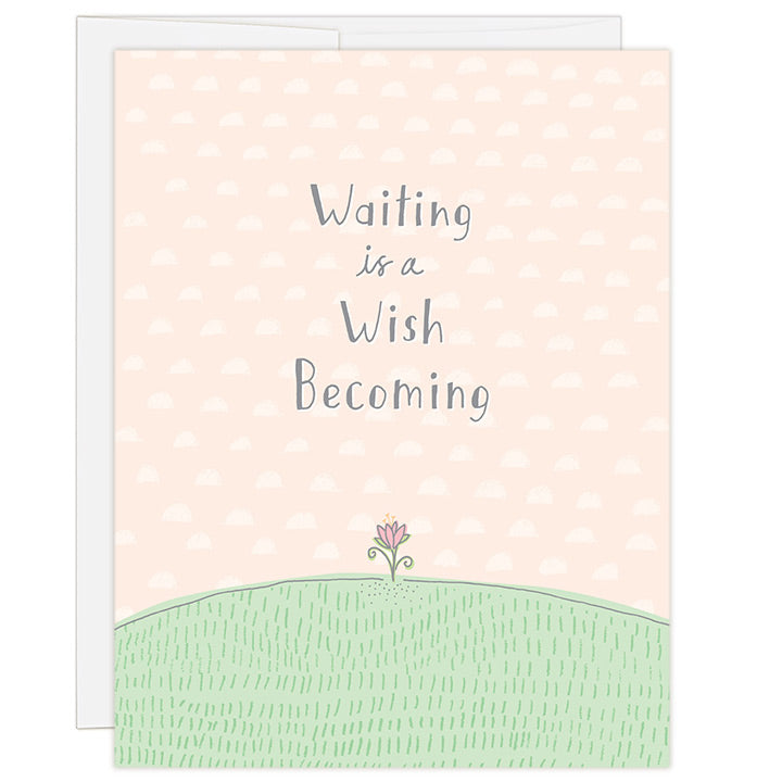 4.25 x 5.5 inch greeting card. Blank inside. Simple and charming illustration style. Title Waiting is a Wish Becoming. Main image is a small hand drawn pink flower poking out of green grass. Background is light peach with a hand drawn pattern of small half moons. Adoption greeting card for encouraging an adopting family along the wait for a child.