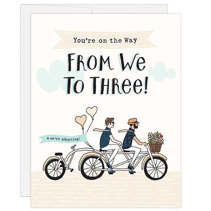 4.25 x 5.5 inch greeting card. Blank inside. Simple and charming illustration style. Title You're on the Way From We to Three! Sub title *we're adopting! Main image is two men on a tandem bicycle, both with neck ties that are blowing in the wind and a third wheel back seat is empty. There are flowers in the basket and balloons on the back with the words we're adopting!