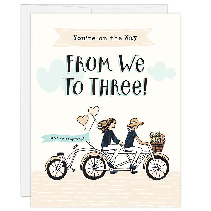 4.25 x 5.5 inch greeting card. Blank inside. Simple and charming illustration style. Title You're on the Way From We to Three! Sub title *we're adopting! Main image is two women on a tandem bicycle. The woman in front is wearing large brim hat and the woman in back is wearing a head band and has long hair. The third wheel of the bike has a back seat and it is empty. There are flowers in the basket and balloons on the back of the bike with the words we're adopting!