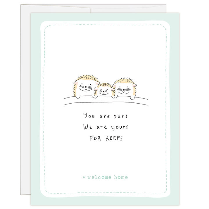 4.25 x 5.5 inch greeting card. Blank inside. Simple illustration style. Title You are ours We are yours FOR KEEPS. Sub title *welcome home. Main image is two adult hedgehogs on either side of one child hedgehog. All three are tucked in bed with covers up to their tiny paws. Light green hand drawn border around a mostly white card.