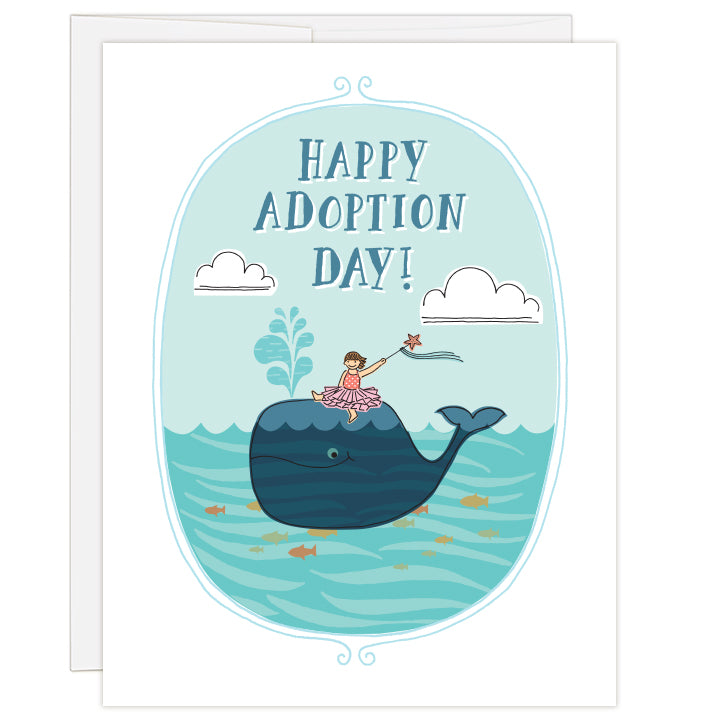 4.25 x 5.5 inch greeting card. Blank inside. Colorful line illustration of a wand-waving little girl sitting atop a smiling whale in an ocean of swimming fish. Colors are blues and pinks, with orange and yellow fish. Illustrated text reads: Happy Adoption Day!