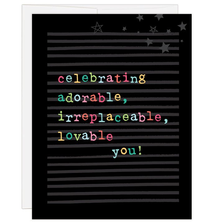 4.25 x 5.5 inch greeting card. Blank inside.  Cover is black and gray striped background with neon-coloring typewriter style letters and a sprinkle of stars. Text reads: celebrating adorable, irreplaceable, lovable you!
