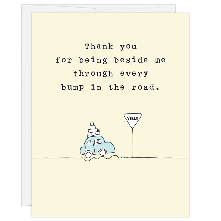 4.25 x 5.5 inch greeting card. Blank inside. Artfully simplistic line drawing of a blue, luggage-laden car driving along a bumpy road and coming to a yield sign. Pale yellow background. Typewriter text reads: Thank you for being beside me through every bump in the road.