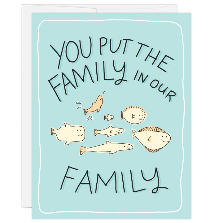4.25 x 5.5 inch greeting card. Blank inside. Cover art is simple line illustration of seven fish swimming together. Fish are different shapes and styles with one fish joyously splashing upward. Cream fish on a teal background. Text: you put the family in our family.