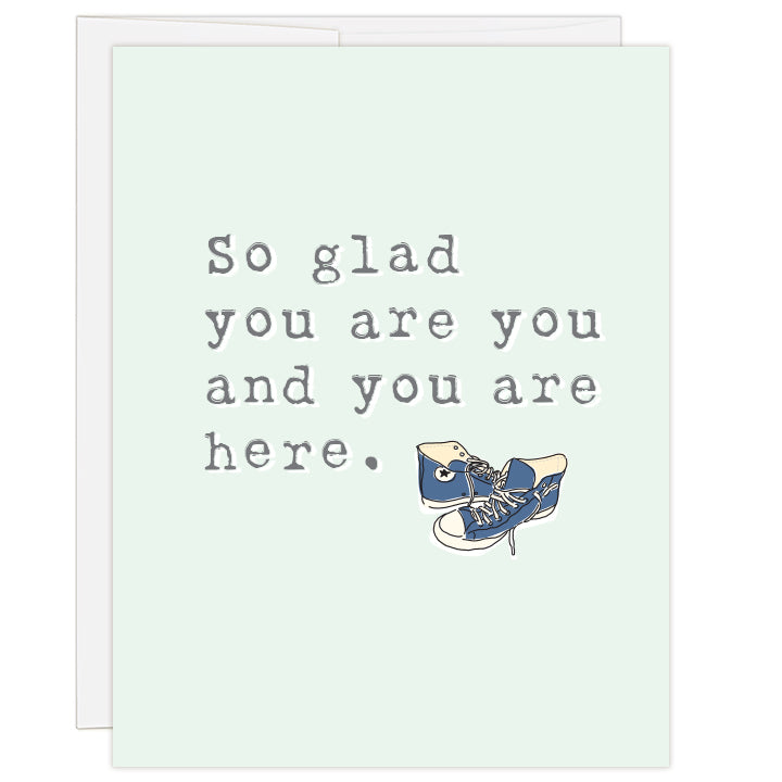4.25 x 5.5 inch greeting card. Blank inside. Cover is pale green with gray lettering and colored line illustration of a pair of blue high-top tennis shoes. Typewriter text reads: So glad you are you and you are here.