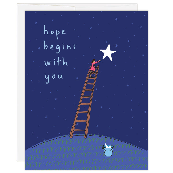 4.25 x 5.5 inch greeting card. Blank inside. Simple line illustration features woman atop a ladder reaching toward a large star in a star-filled night sky. At the foot of the ladder rests a bucket holding a star. Shades of blue. Text reads: hope begins with you.
