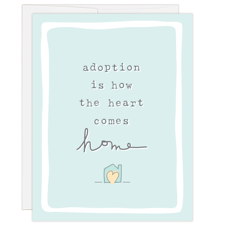 4.25 x 5.5 inch greeting card. Blank inside. Front of card features light blue background with simple line drawing of a small house with a yellow heart inside. Text reads: adoption is how the heart comes home.