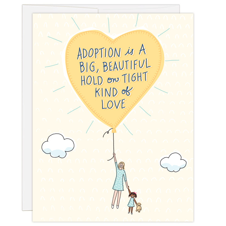 4.25 x 5.5 inch greeting card. Blank inside.  Cover art is a bright yellow balloon lifting up a caucasian mother and African American child, child holding a teddy bear all on cream background. Hand-illustrated text reads: Adoption is a big, beautiful hold on tight kind of love.