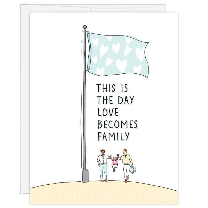 4.25 x 5.5 inch greeting card. Blank inside. Cover features simple line illustrations of two dads lifting up a young child between them. Family beneath a flag filled with white stars. Soft colors of teal and yellow against a white background. Text reads: This is the day love becomes family.