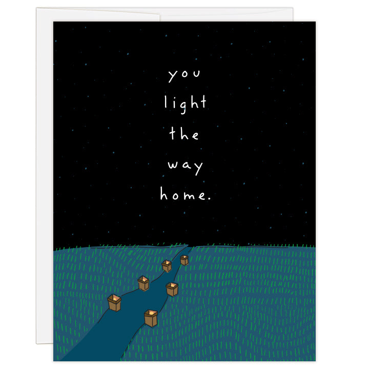 4.25 x 5.5 inch greeting card. Blank inside. Cover features line illustration of a path lit by luminaries beneath a blue-black star-filled sky. Text reads: you light the way home.