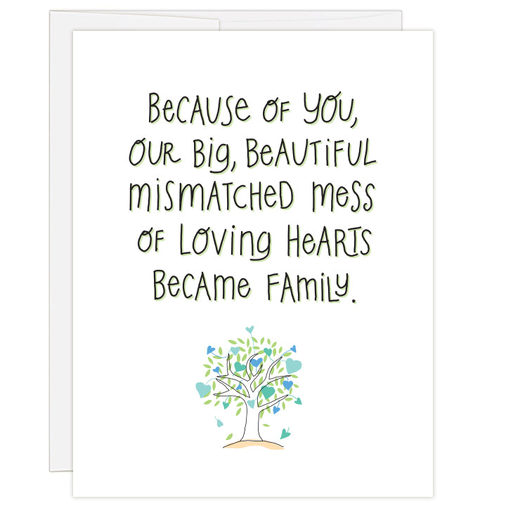 4.25 x 5.5 inch greeting card. Blank inside.  White cover background with line illustration of tree with different shaped and colored hearts in shades of blue. Large hand-illustrated text reads: Because of you, our big, beautiful mismatched mess of loving hearts became family.