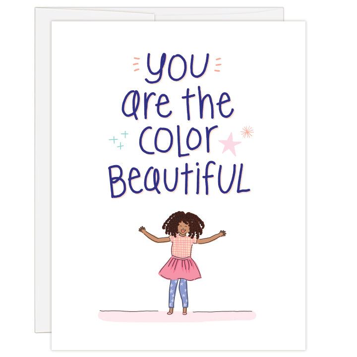 4.25 x 5.5 inch greeting card. Blank inside. Cover features bold headline above adorable African American girl in pink skirt, plaid shirt and blue starry leggings. Text reads: you are the color beautiful.