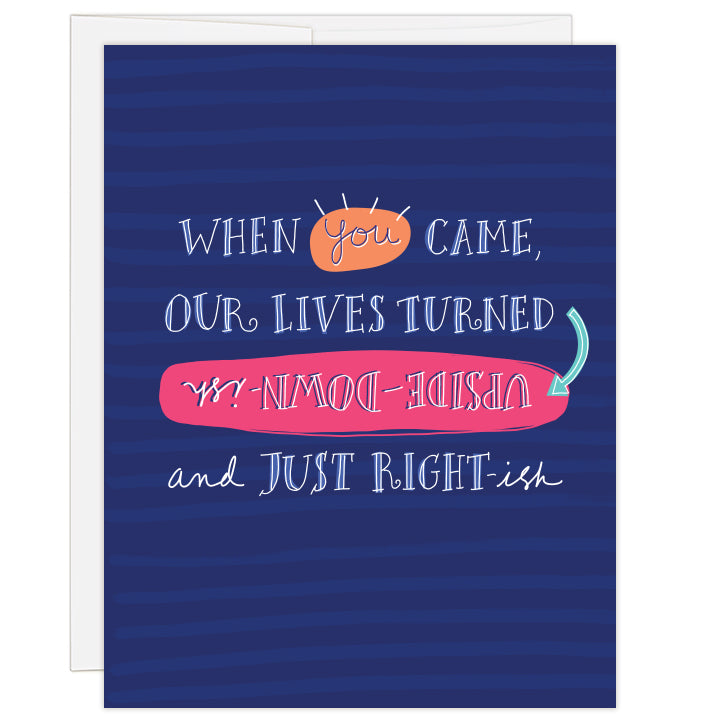 4.25 x 5.5 inch greeting card. Blank inside.  Cover background stripes in shades of blue with big white text selectively called out with colors reading: When you came our lives turned upside-down-ish and just right-ish.
