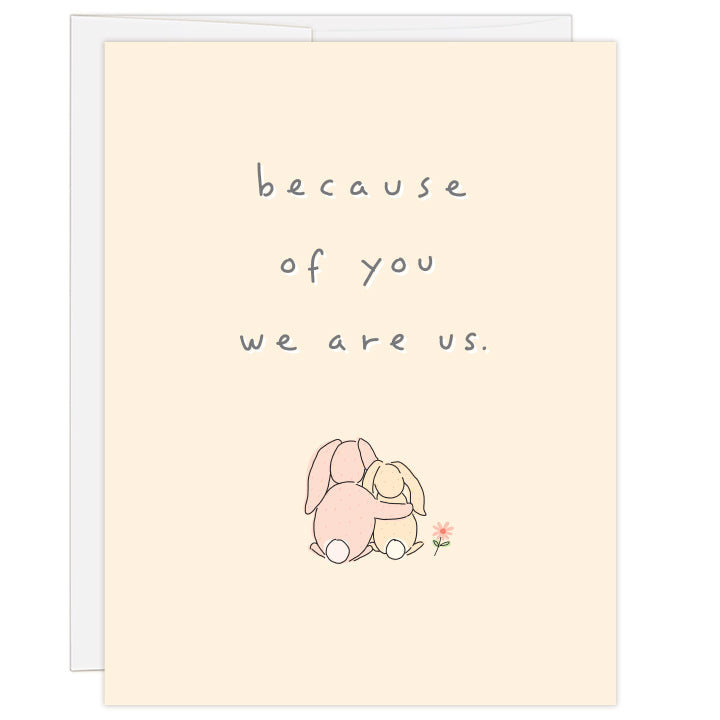 4.25 x 5.5 inch greeting card. Blank inside.  Simple and charming line illustration of one bunny with arm around smaller bunny, as seen from behind, with small flower to the side. On pale peach background. Text: because of you, we are us.