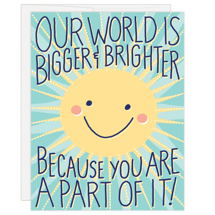 4.25 x 5.5 inch greeting card. Blank inside.  Illustrated cover art is a bright yellow sun with smiling face on a teal background with artful sun rays. Text: Our world is bigger and brighter because you are a part of it!