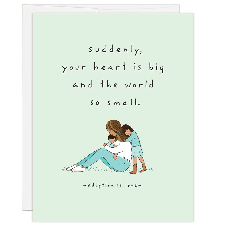 4.25 x 5.5 inch greeting card. Blank inside.  Cover art is an intimate illustration of a mother of color with her two children of color. Mother hugging child, with older child leaning against mother. Simple line illustration on pale green background. Text: suddenly, your heart is big and the world so small. adoption is love.