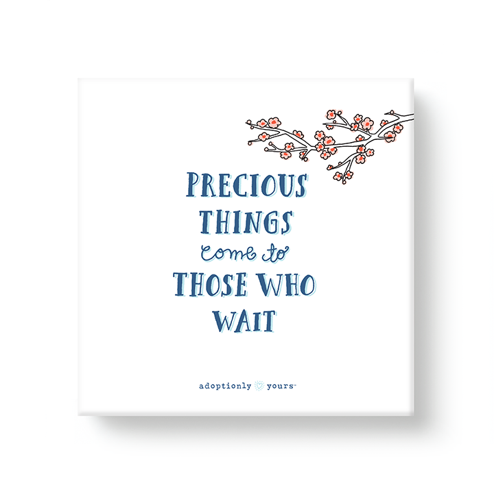 6 by 6 inch canvas wrap with 1.25 depth. Back of canvas with hard-sealed backing and hanging brackets. Simple and charming illustration style art wraps around the sides of frame. Title Precious Things come to Those Who Wait. Drawing of child with pig tails standing in sea shell paddling water. Cherry blossom branch above child. Four sides are light blue and white checkerboard pattern. Small adoptionly yours words and logo below border of artwork.