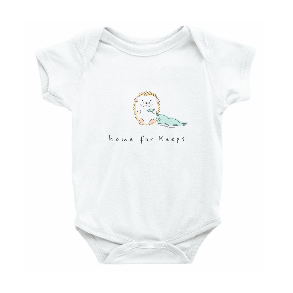 White 100% combed ringspun cotton with reinforced 3-snap closure. Small graphic in the center of the onesie of simple and charming hand drawn hedgehog sitting and holding the corner of a mint green baby blanket. Below the hedgehog are hand drawn words in black that read home for keeps.
