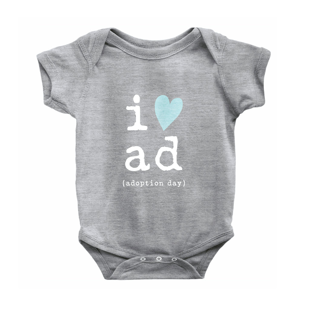 Gray 93% cotton 7% polyester with reinforced 3-snap closure. Graphic is in center of onesie in white typewriter font with the letter i and a blue heart graphic. Stacked underneath are the letters a and d in white typewriter font. Below a and d are the words in white typewriter font  and reads (adoption day).