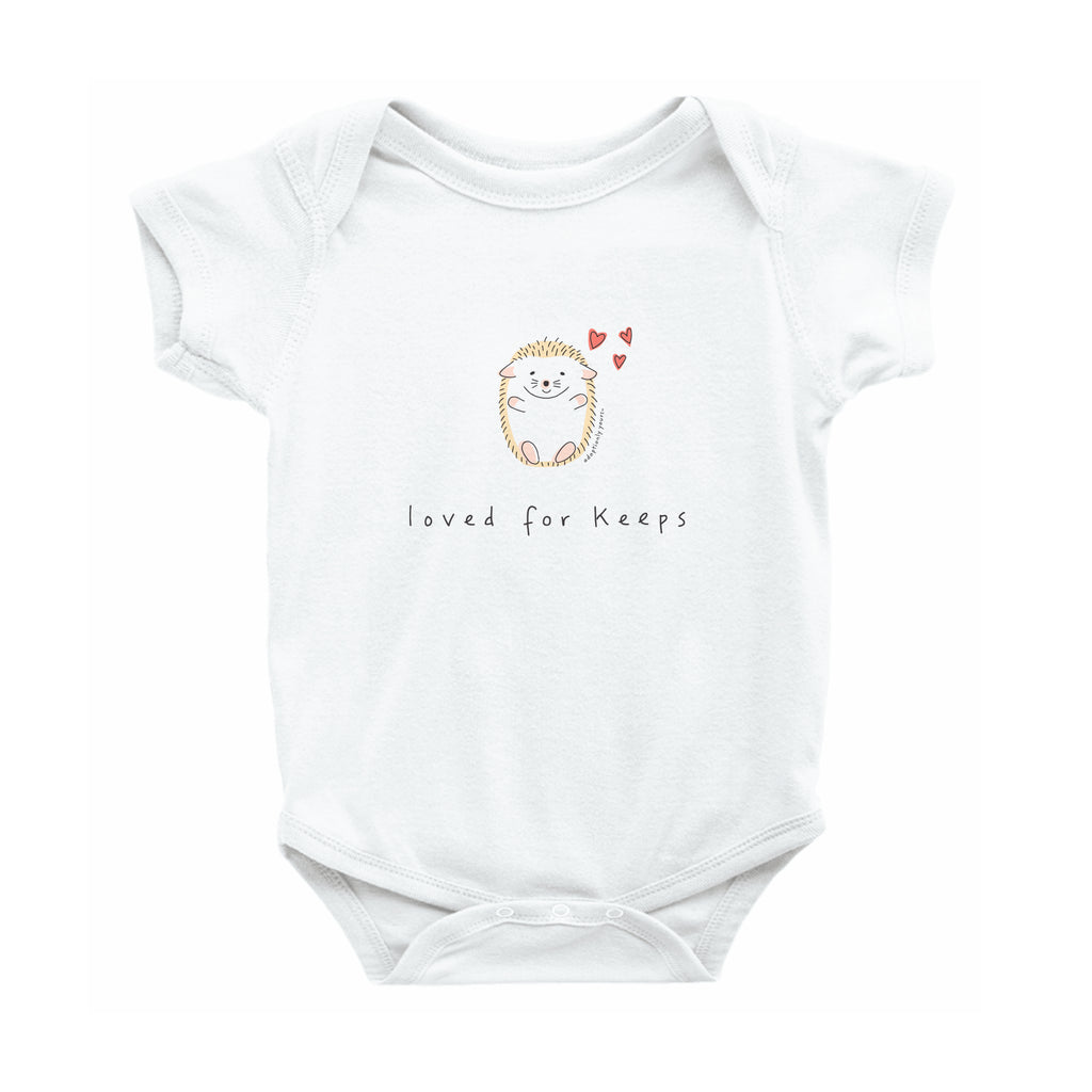 White 100% combed ringspun cotton with reinforced 3-snap closure. Small graphic in the center of the onesie of simple and charming hand drawn hedgehog sitting with arms outstretched and 3 small red hearts floating above his head. Below the hedgehog are hand drawn words in black that read loved for keeps.