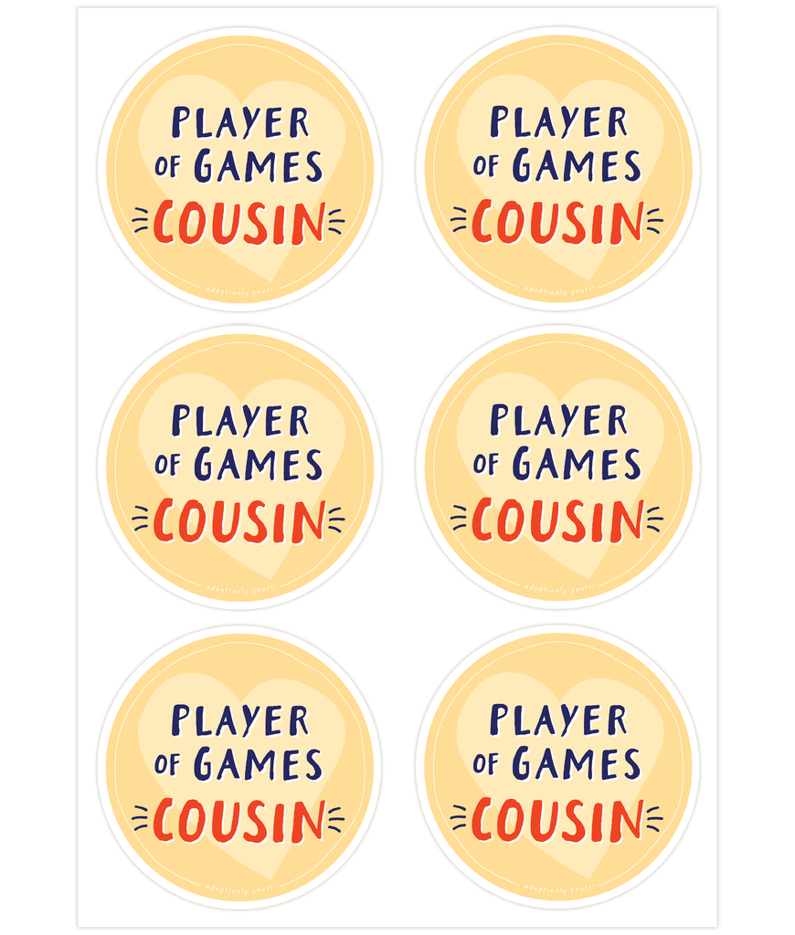 4 and 1/8 inch round durable matte vinyl weather resistant sticker. Easy to apply and reapply. 1/8 inch white border. Background is bright yellow with lighter yellow hand drawn heart. Hand illustrated words in dark blue read Player of Games. Below is the word Cousin in bright red with dark blue dashes on each side. In tiny casual font the words adoptionly yours tm are part of a thin white hand drawn border.